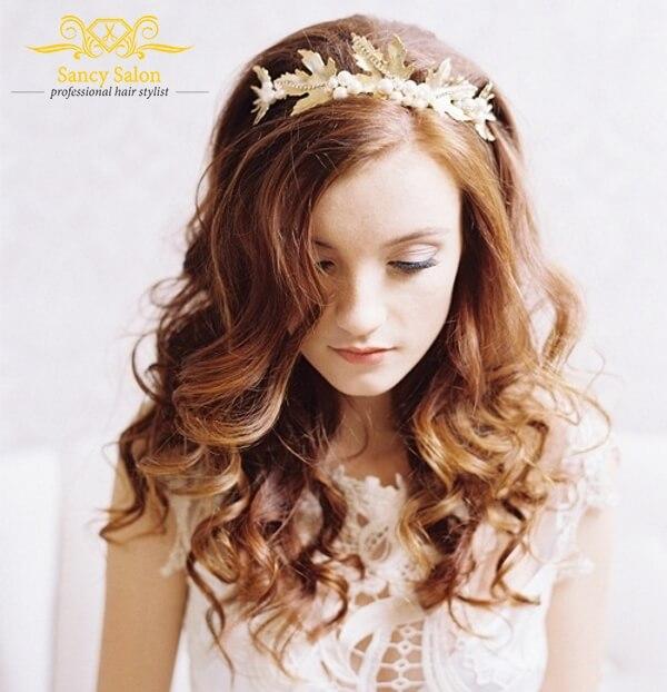 Kiểu tóc cô dâu uốn xoăn kết hợp bờm hoa lá đội đầu.